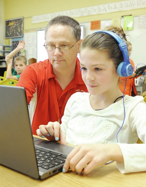 Anthony Weber | Troy Daily News Forest Elementary School teacher Bill Hewitt works with third-grade students, including Hannah Beck, on Tuesday during a lesson on telling time at the school in Troy.