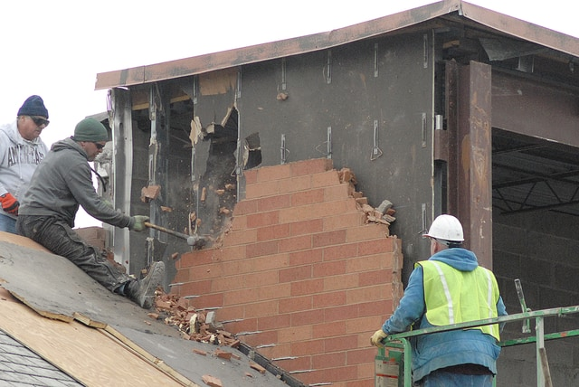 Anthony Weber | Troy Daily News Workers bring down a wall of bricks at the corner of the former Kroger location and the Asian Cottage restaurant Tuesday in Troy. The site will allow for more parking after demolition is completed.