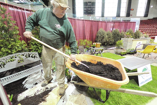 Anthony Weber | Troy Daily News Andy Sherick of Greentech Lawn and Irrigation spreads mulch around a display in preparation for the 2016 Miami County Home and Garden Show at Hobart Arena in Troy. According to Sherick, Greentech will offer several seminars on pest control during the event throughout the weekend. Show hours are 2-7 p.m. Friday, 11 a.m. to 7p.m. Saturday and 11 a.m. to 4 p.m. Sunday.