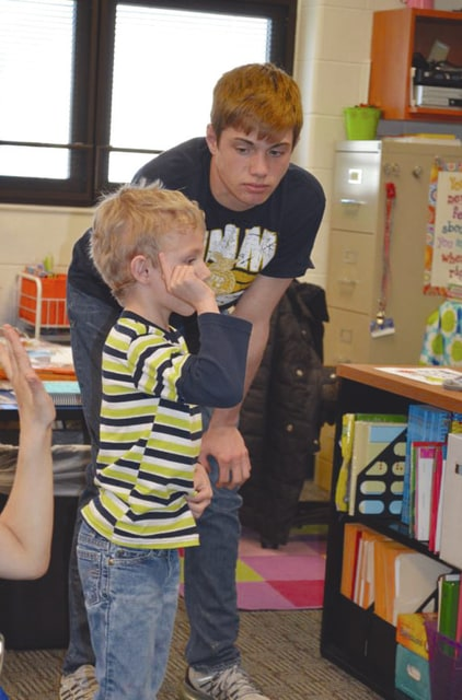 Provided photo Alex Isbrandt helps a kindergartner in Mrs. Stephanie Larson's class play a wildlife game as part of Project Wild.