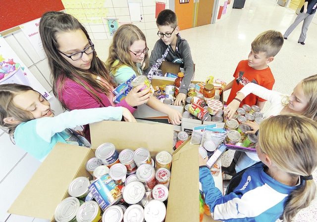 Anthony Weber | Troy Daily News Hook Elementary School fifth-grade teacher and student council adviser Greg Gustin gave students a food drive challenge following a recent class discussion of what to donate and what not to donate to food drives. Students from left, including Sera Halter, Marlee Cupp, center, Lexy Oldham, Gabe Long, Maxwell Berning, Lillian Graham and Aubrey Murphy, organize donations. According to Gustin, the food-drive will continue through Tuesday and deliveries will be made Wednesday into the community, including the Lincoln Center, Franklin House, St. Patrick Soup Kitchen, several churches and some Hook families that could use support during the holiday season.