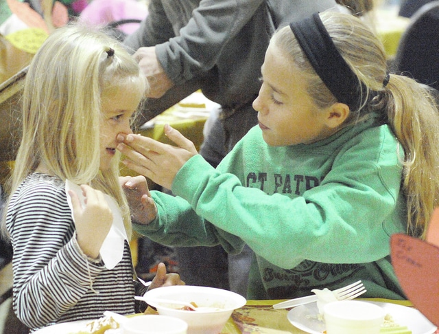 Anthony Weber   Troy Daily News Eva Dexter, 10, wipes the butter off the nose of her sister, Lauren, 4, while families sit down together during a program at St. Patrick School on Tuesday.. Both were enjoying a meal with their family during a preschool feast inside the Parish Center on Tuesday in Troy.
