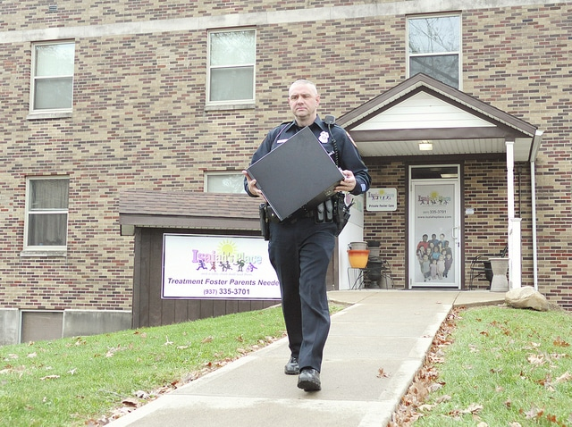 Anthony Weber | Troy Daily News Officers from the Troy Police Department remove items during a search warrant at the office of Isaiah's Place, a suite inside the Stouder Center, on Wednesday in Troy.