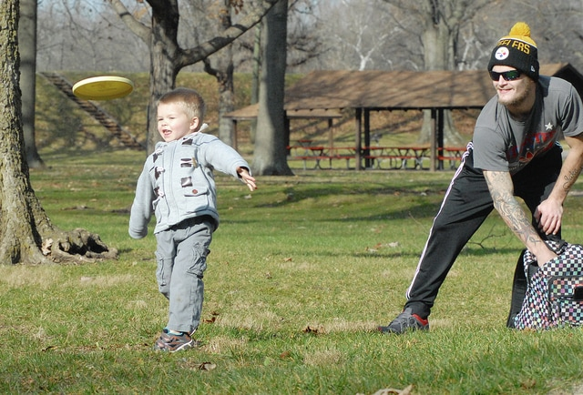"Anthony Weber | Troy Daily News Jordon Satterfield and his son, Jake, 3, along with Ashley Fulp (not pictured) play a game of disc golf Wednesday at the Troy Community Park. ""We play as much as we can,"" Satterfield said. ""I've played through the winter, though,"" he added. Temperatures rose to nearly 60 degrees for the second day in a row, but will be much cooler today."