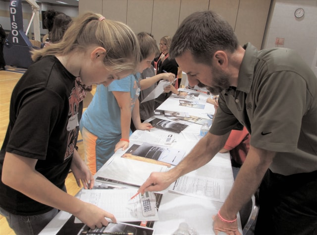 Matt Erwin of Erwin Chrysler Dodge Jeep, helps students find the right vehicle to fit their budget during the Kids to College budget simulation on Friday.