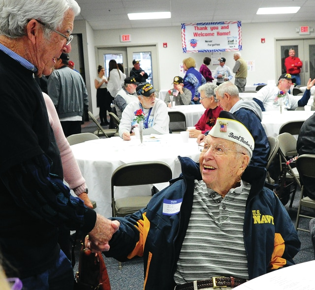 "Mike Ullery | Daily Call Pearl Harbor survivor and Fairborn resident Rolla ""Ed"" Malan, 96, greets a guest at a recent Honor Flight Dayton reunion in Springfield."