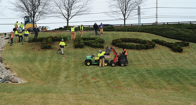 Mike Ullery | Civitas Media Workers from several local landscape companies put the finishing touches on a landscape project in the southwest quadrant of the Interstate 75 and State Route 41 interchange on Wednesday morning. Workers used 180 Winter Gem Boxwood shrubs to spell out T-R-O-Y in 18-foot high letters that will be visible to northbound traffic on I-75.