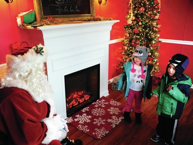 Mike Ullery | Civitas Media Three-year-old twins Mackenzie and Grant Moyer of Troy size up Santa Claus before getting too close at Santa's House on Prouty Plaza in Troy on Thursday.