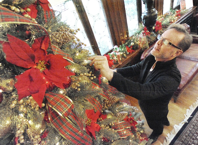 "Anthony Weber | Troy Daily News  David Fair decorates a Christmas tree in the study Thursday as the Troy-Hayner Cultural Center prepares for the Christmas season. The theme for this year's holiday spirit is ""Christmas Legends"" which will be displayed throughout the Christmas season. Saturday is Children's Day at the Hayner beginning at 1 p.m. The grand opening for the Christmas décor is Sunday beginning at 1 p.m."