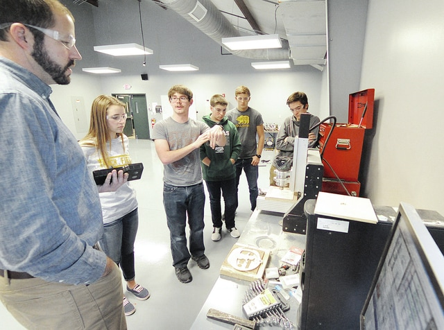 Anthony Weber | Troy Daily News Students of Jared Mitchell's CAD-1 class at Troy Christian High School work on creating Christmas ornaments using a 3-D modeling concept and a CNC machine Friday at the school.
