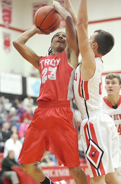 Anthony Weber/Troy Daily News Troy's Zion Taylor shoots as Tippecanoe's Quenten Williams defends Tuesday night.