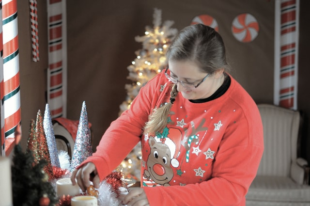 """Cecilia Fox   Troy Daily News Karrie Platfoot adjusts the decorations in the 120 square foot tiny house she has designed and built herself. The little home on wheels, called """"Tiny Teal,"""" was part of the annual Tippecanoe Christmas in the Village Home Tour, which showcases Tipp City homes that have been decorated for the holiday. Platfoot decorated Tiny Teal to look like a gingerbread house."""