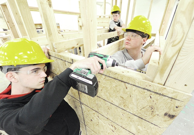 Anthony Weber | Troy Daily News Students of Jim Kitchen's Home Building class, including seniors Tommy Fischer, left, Alex Hornbeck, right, and junior Matt Taylor, background, work on constructing a tiny house. According to Kitchen, the house is expected to be completed in late May.