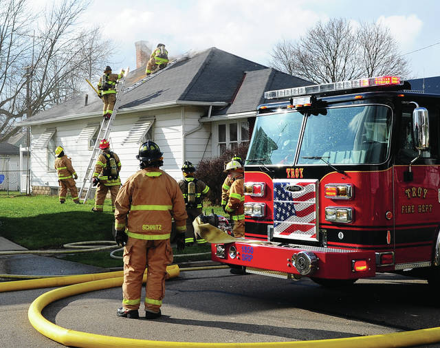 Mike Ullery | Daily Call Troy and Tipp City firefighters work to extinguish a fire at 1002 South Clay Street in Troy on Tuesday afternoon.