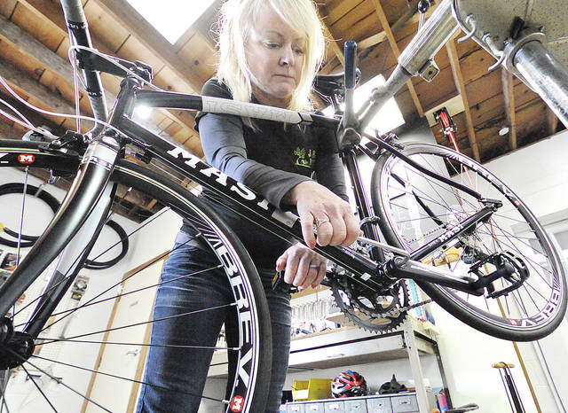 Anthony Weber | Troy Daily News Joyce Ferguson of the J & D Bicycles shop works on maintenance of a bike, including crank bolt tightening recently at the shop on Elm Street in Troy.