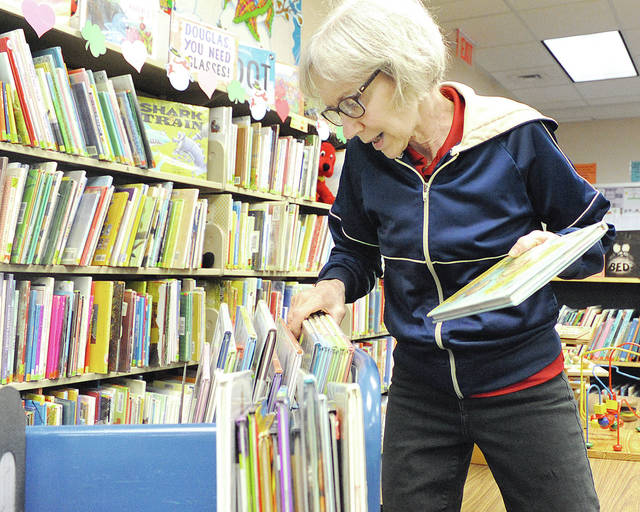 Anthony Weber | Troy Daily News Milton-Union Public Library Director Carol Netzley Coate puts books back on the shelf in the childrens area of the library recently in West Milton. Coate will be retiring after 25 years of service.