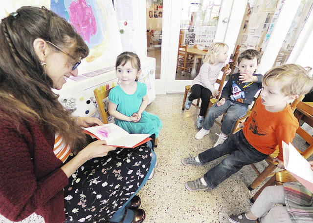 Anthony Weber | Troy Daily News Children at the Overfield School have been engaged in poetry this week with Artist in Residence Nancy Kangas from Columbus. During her two-week residency at the school, Kangas has helped students express their ideas in poetic form. According to Kangas, children have experienced the fun of words while combining sensory information to create poems. Here, Kangas shares each of the poems with 3- and 4-year-old students, including Miri Patton on Thursday during her visit through a grant from the Ohio Arts Council. Children have created works on a broad range of topics, including hockey, wood chippers, animals and magic. Rhythm and pattern are important components of poetry and also excellent tools for early literacy development.