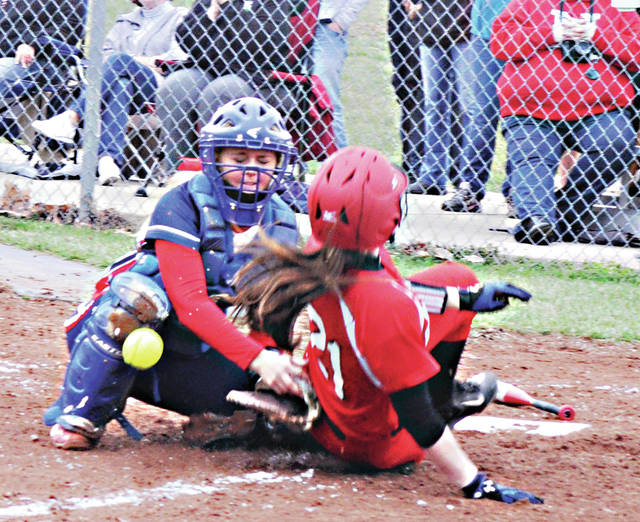 Rob Kiser/Civitas Media Piqua catcher Rayna Brownlee reaches for the throw as Newton's Brooke Deeter slides across the plate Monday.