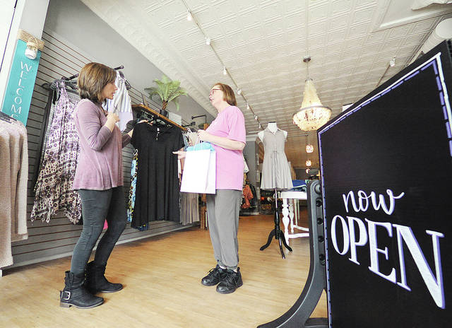 Anthony Weber | Troy Daily News Your Dream Boutique owner Angela Kirby assists customers including Mary Ann Bick with a dress Thursday in Troy. Your Dream Boutique is located at 5 East Main Street near the Public Square.