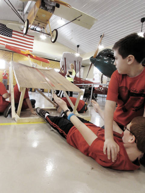 "Parker McKee holds down teammate Ian Bayer as they pull a sling shot to launch their aircraft during a ""Take Flight"" challenge event at WACO Air Museum and Learning Center."