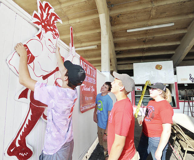 Anthony Weber | Troy Daily News Newton High School band members including, from left, Clark Yoder, Sam Tackett, Will Yoder and Jalynn Mead work on preparations Thursday for opening the cafeteria at the Miami County Fairgrounds. The Newton Band Booster Cafeteria, which has served meals since 1975 during the fair, will open its doors Friday for breakfast, lunch and dinner at the stadium during the 2017 Miami County Fair.