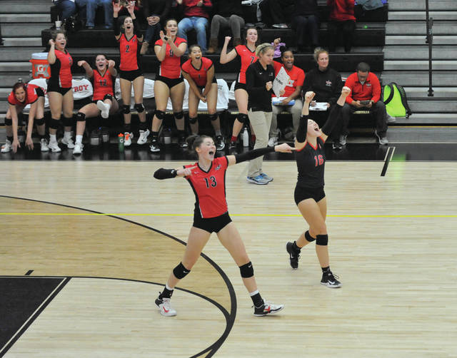 Josh Brown/Troy Daily News Troy's Lauren Schmitz (13), Alexa Holland (16) and the Troy bench celebrate a point during a long third-set run in Wednesday's Division I sectional final against Beavercreek at Centerville High School.