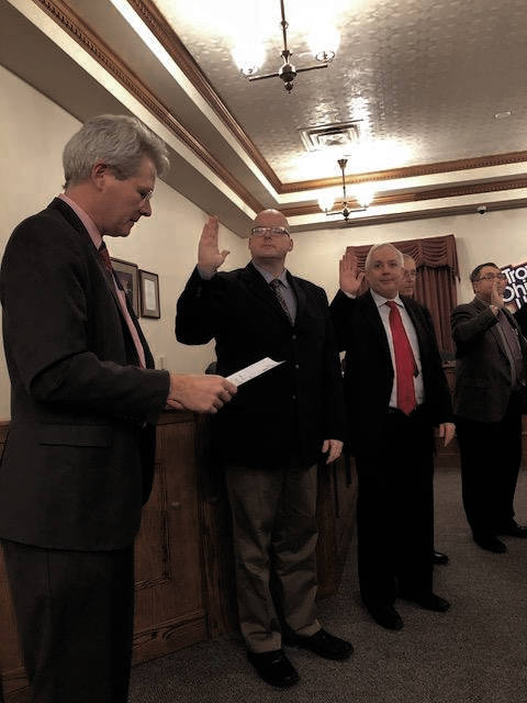 From left, City law director Grant Kerber administers the oath of office to council members, including William Lutz and Todd Severt, on Thursday.