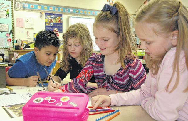 Cody Willoughby | Troy Daily News Left to right, Brian Lomeli, Scarlett Deeter, Addy Harman, and Kyndall Seitz work together on a poster to promote Miami Valley animal adoption at Concord Elementary on Friday in Troy.