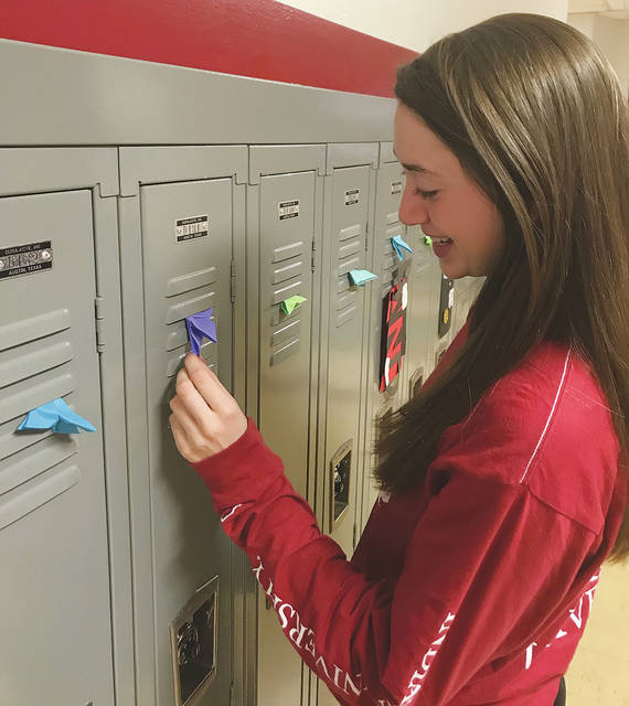 David Fong | Troy Daily News Troy High School freshman Hallie Westmeyer looks at one of the origami butterflies a mystery student left on every locker in the school Tuesday morning.