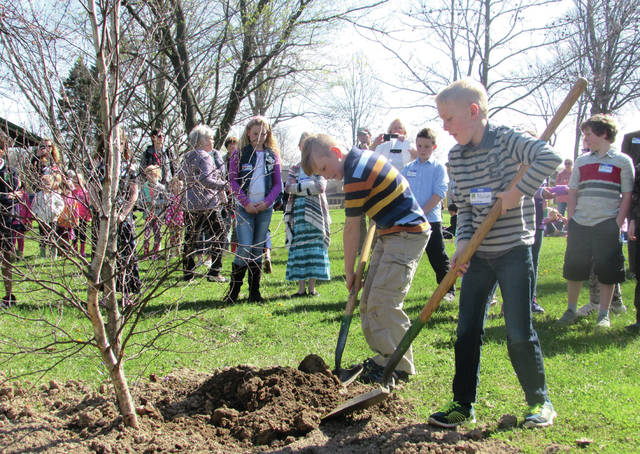 Cody Willoughby   Troy Daily News Third graders Owen Poeppelman and Nolan Riethman of Concord Elementary shovel topsoil onto a new tree planted for Arbor Day on Friday at Menke Park in Troy.