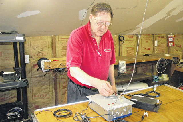 Cody Willoughby | Troy Daily News Larry Kiser, president of Kiser Industries, LLC, switches on an LED strip of his patented tandem lighting system at his private workshop in Troy.