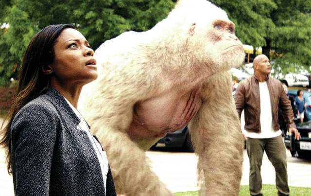 "Provided photo Naomie Harris and Dwayne Johnson, alongside a mutated gorilla named George, face off against the incoming threat in ""Rampage."""
