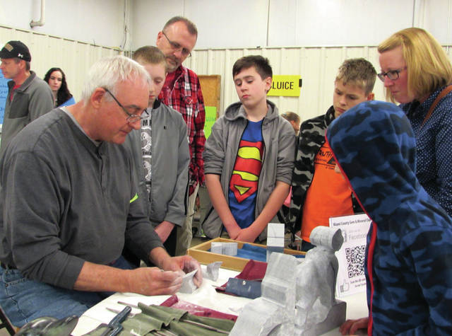Cody Willoughby | Troy Daily News Terry Lukac demonstrates soapstone carving to, left to right, Brady McKee, Ron McKee, Parker McKee, Logan Newhouse, Megan McKee, and Alex Newhouse during the 35th annual Gem and Rock Show on Saturday at the Miami County Fairgrounds.