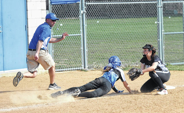 Mike Ullery/AIM Media file Miami East coach Brian Kadel races to watch a play as Covington third baseman Kristie Barnes puts the tag on Miami East's Sam Urban during a game earlier this season.