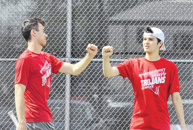 Josh Brown/Troy Daily News Troy's Andrew Magoteaux (left) and Shane Essick bump fists after a point during a match at the Division I sectional tournament Wednesday in Troy.