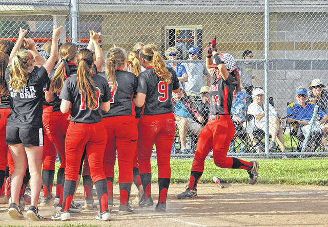 Josh Brown/Troy Daily News Newton's Kylee Fisher is greeted at home plate by her teammates after she hit a solo home run in the bottom of the sixth inning in the Division IV sectional final against Russia Tuesday at Bradford.
