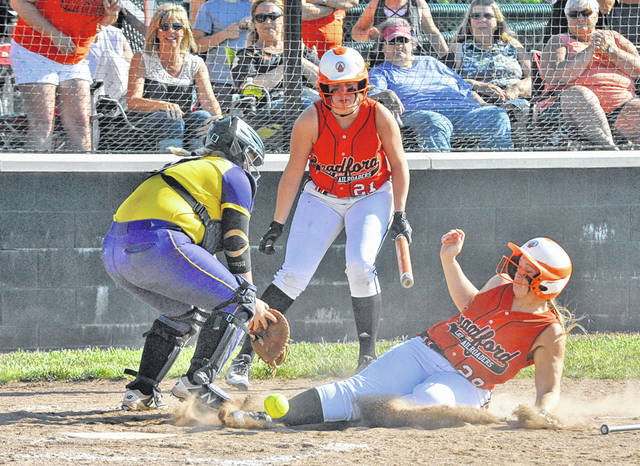 Josh Brown/Troy Daily News Bradford's Aspen Weldy (28) slides in safely at home as teammate Bianca Keener (21) looks on in a Division IV regional semifinal game against Mechanicsburg Wednesday in Greenville.