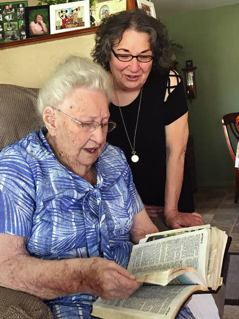 Melody Vallieu | Troy Daily News Alice Lucas reads a passage from her Bible to her daughter Donna Harris recently in their Troy home.