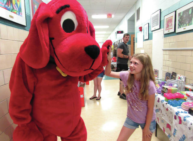 Cody Willoughby | Troy Daily News Fourth grader Keilie Slattery gives a high five to Clifford the Big Red Dog during the family book fair Thursday at Forest Elementary in Troy. Students were invited to bring their parents and grandparents to the event, where thousands of books were available to purchase. A pictorial slideshow was on display in the gymnasium featuring events from the 2018-19 school year, as well as refreshments available on the premises from Kona Ice.