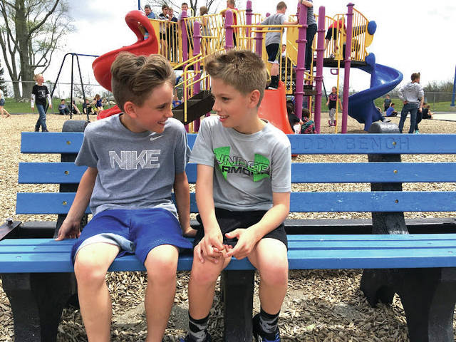 "Cody Willoughby | AIM Media Midwest Third graders Ty Rohrer, left, and Lincoln Littlejohn chat on a ""Buddy Bench"" on Friday at Miami East Elementary. The benches were installed last month, as part of a project sponsored by the Miami East Elementary Parent Teacher Organization."
