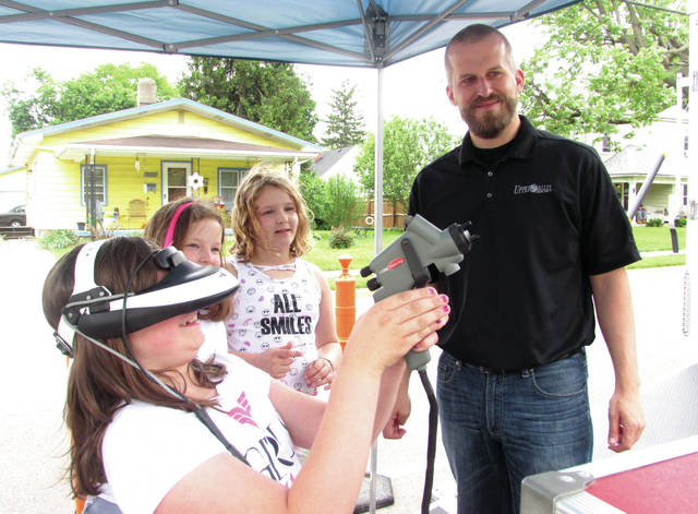 "Cody Willoughby | Troy Daily News Third grader Chloe McBride participates in virtual-reality car painting with UVCC recruitment coordinator Andrew Snyder during ""Career on Wheels"" on Friday at Heywood Elementary."