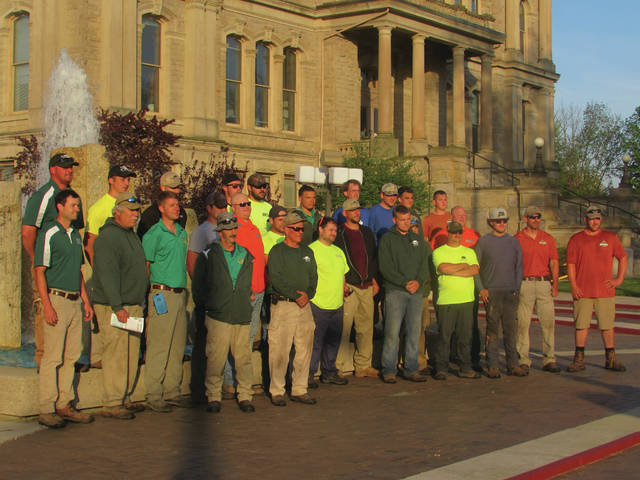 Cody Willoughby | Troy Daily News Members of Operation Cloverleaf, comprised of seven local lawn and landscaping companies, pose following the re-mulching and maintenance of the Miami County Courthouse property on Wednesday in Troy.