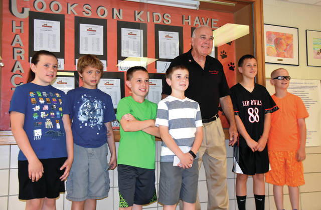 Cody Willoughby | Troy Daily News Left to right, Fourth graders Josie Woodell, Micah Pyles-Dodds, Cayden Wesco, Nate Reynolds, Brady Campbell, and Tobey Seibert present a check to Honor Flight Dayton representative Larry Blackmore on Friday at Cookson Elementary in Troy.