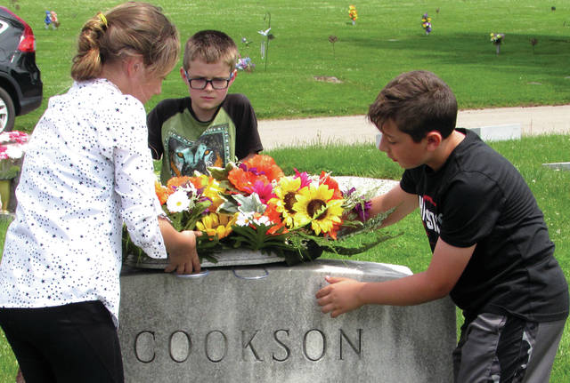 Cody Willoughby | Troy Daily News Left to right, Hayden Taylor, Brayden Maylone, and Connor Haywood adorn the Cookson grave site with a flower arrangement on Thursday at Riverside Cemetery in Troy.