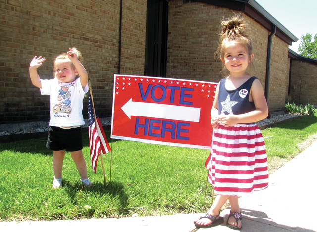 Cody Willoughby | Troy Daily News Ellie Compton, 2, of Troy, and Allison Herron, 4, of Troy revel in their triumph after casting a vote on Tuesday at the Riverside of Miami County children's polling location in Troy.
