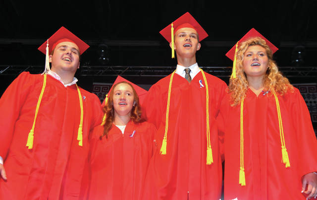 Cody Willoughby | AIM Media Midwest Ensemble members Riley Moore, Abigail Innes, James Boezi, and Brooke Klopfenstein lead their fellow graduates in a rendition of the Troy High School Alma Mater during the Troy High School class of 2018's graduation ceremony on Saturday at Hobart Arena.
