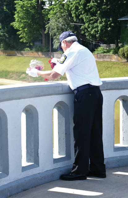 Cody Willoughby | Troy Daily News Gary Hickerson of the United States Marine Corps dispenses rose petals from the Adams Street Bridge during the Memorial Day Ceremony on Monday in Troy.