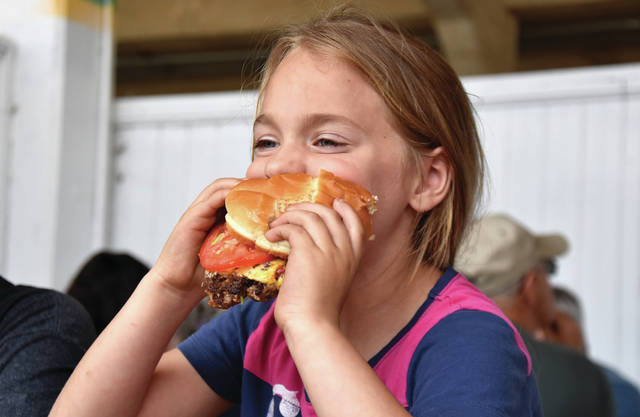 Cody Willoughby | Troy Daily News Karma Williamson, 6, of Piqua bites into a burger during the 4th annual Food Truck Rally & Competition on Saturday, May 19 at Miami County Fairgrounds. This year's rally hosted 54 food trucks, up from 30 food trucks in the event's 2015 premiere. Participating trucks came from throughout the Miami Valley, as well as the Columbus, Springfield, and Cincinnati areas, and surrounding states. For more information, visit Miami County Food Truck Rally & Competition on Facebook.