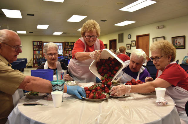 Cody Willoughby | Troy Daily News Neda Davidson, center, dumps newly cleaned strawberries for volunteers Bob Gilburg, Jan Payton, Susie McKee, and Terry Millhouse to de-stem at the Troy Senior Citizens Center on Thursday.