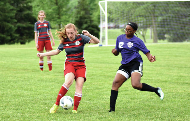 Cody Willoughby | Troy Daily News Isabella Wait of Troy and Amari Bradford of Butler United vie in the Troy Strawberry Soccer Invitational on Saturday.